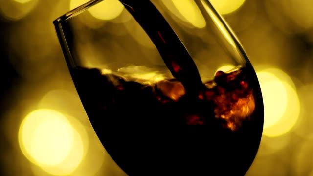 rotwein aus der flasche gießen. sommelier gießt einen ausgezeichneten rosenwein in glas. - cabernet sauvignon traube stock-videos und b-roll-filmmaterial
