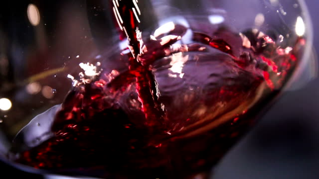 Red wine pouring in glass slow motion