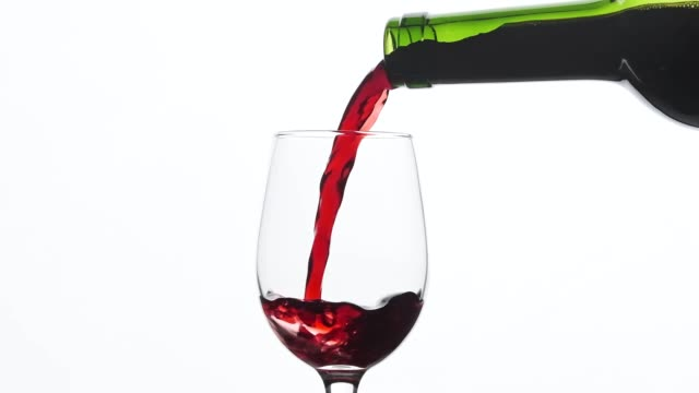 Red wine pouring in wine glass over white background. Close-up shot Red wine pouring in wine glass over white background. Close-up shot. Slow motion of pouring red wine from bottle into goblet. Red wine forms beautiful wave red wine stock videos & royalty-free footage