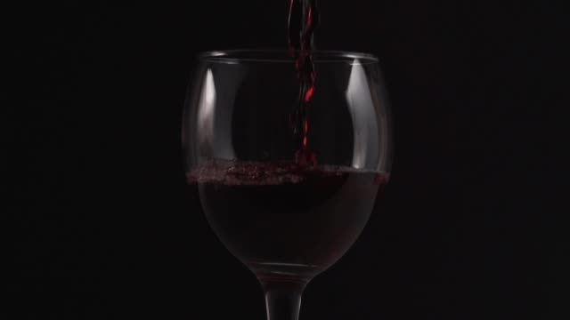 Red wine pours to glass on dark background, slow motion video