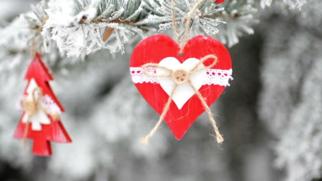 red wooden christmas toys on snow-covered fir in winter park video