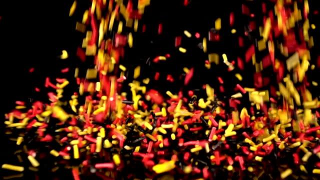 röd, gul, svart strössel faller långsam rörelse. - confetti bildbanksvideor och videomaterial från bakom kulisserna