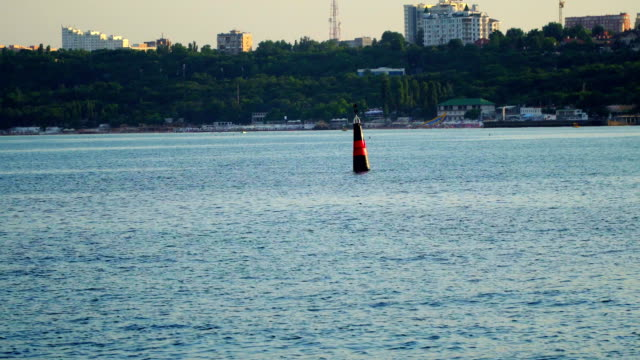 Red-black buoy in sea water as safety warning video