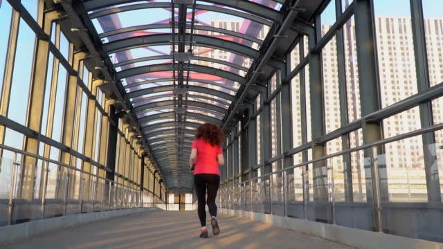 vidéos et rushes de rousse femme athlétique passionnée de jogging en milieu urbain, le mouvement lent - une seule femme d'âge mûr