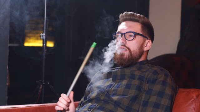 Red-haired brutal man getting pleasure from smoking