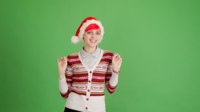 red-haired girl in a santa hat dancing on a green background video