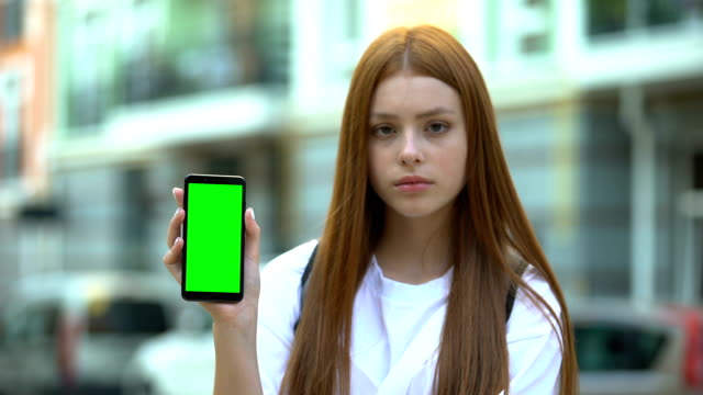 Red-haired girl showing smartphone with green screen, free navigation app