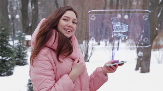 Red-haired girl with hologram shopping cart Beautiful young woman in a winter park interacts with HUD hologram with shopping cart. Red-haired girl in warm pink clothes uses the technology of the future mobile screen market retail space stock videos & royalty-free footage