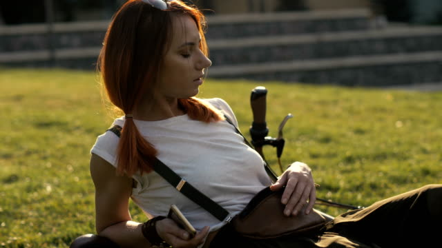 redhaired woman cyclist resting on green lawn in summer park - ragazza auricolari rossi video stock e b–roll