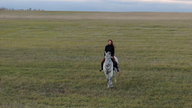 A red-haired woman rides a white horse.