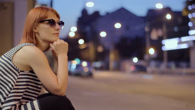red-haired woman sitting on a street at night video