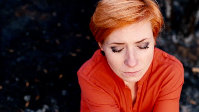 Red-haired woman with a sad face looking at the camera, portrait. Concept: need help, loneliness, depression, dependency video