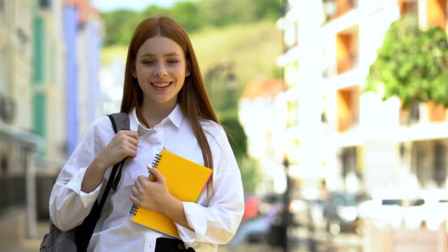 Red-haired young female with rucksack holding books, students life, education