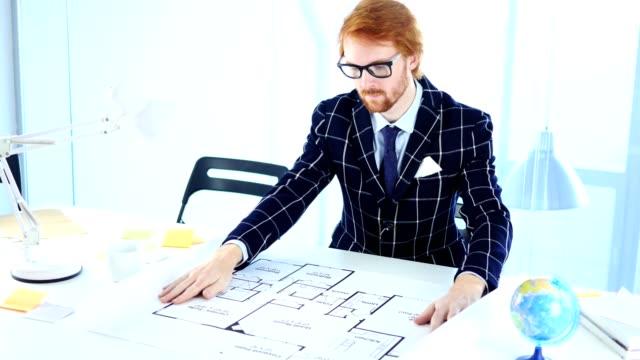 redhead arkitektoniska ingenjör som arbetar på plan i hans kontor - rött hår bildbanksvideor och videomaterial från bakom kulisserna
