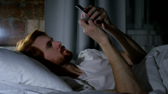 Redhead Beard Man Browsing Email and Messages on Phone in Bed video