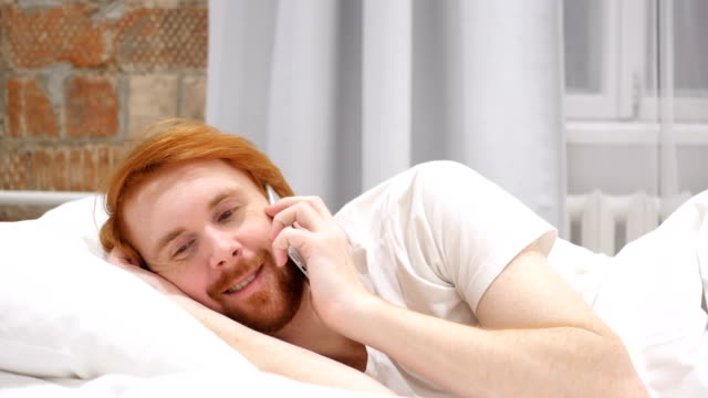 Redhead Beard Man in Bed Dialing call and Talking on Phone video