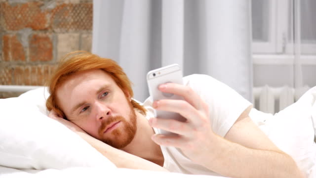 Redhead Beard Man Lying in Bed and Browsing on Smartphone at Night video