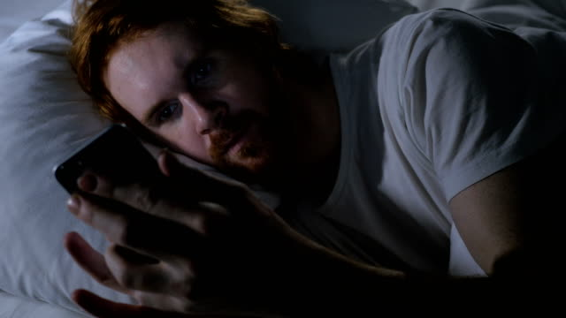 Redhead Beard Man on Smartphone Browsing at Night in Bed video