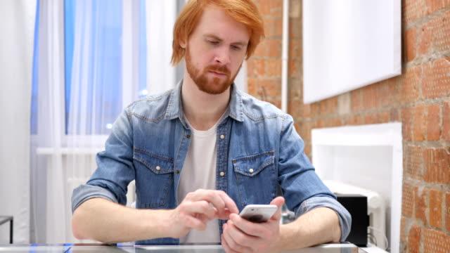 Redhead Beard Man Using Smartphone for Online Browsing Redhead Beard Man Using Smartphone for Online Browsing redhead stock videos & royalty-free footage