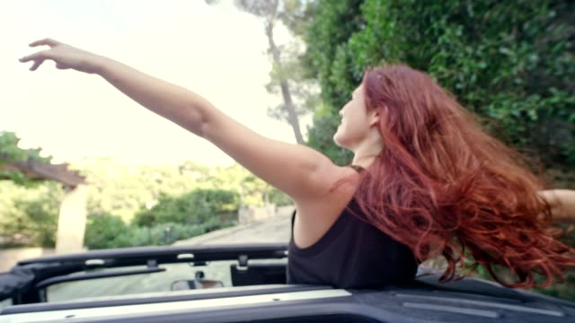Redhead girl having fun in a SUV with sun roof Summer activities. Travelling in a open SUV. Laughing and shouting human hair stock videos & royalty-free footage