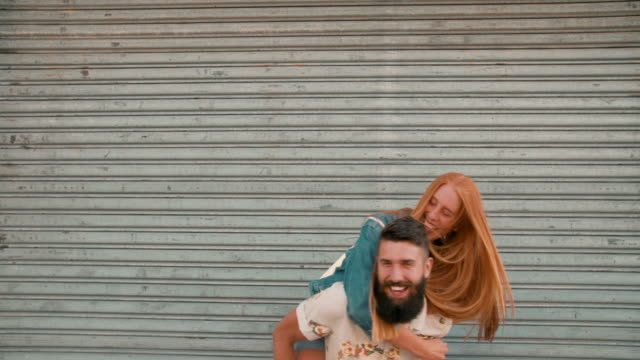 redhead girl laughing loudly while hipster boyfriend piggyback - hipster stock videos and b-roll footage