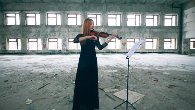 Redhead lady is playing the violin in a stranded building