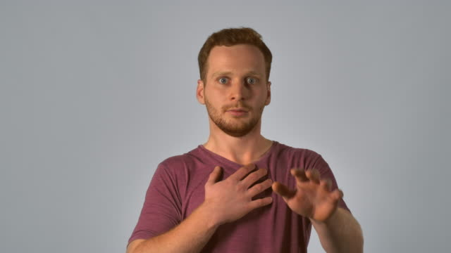 redhead male shows feeling fear caucasian guy with red hair showing emotion fright. handsome redheaded men wearing in casual t-shirt. Portrait ginger young caucasian man on grey background dyed red hair stock videos & royalty-free footage