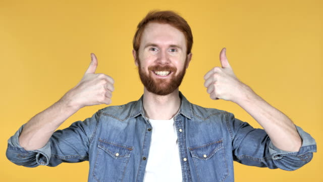redhead man gesturing thumbs up isolated on yellow background - thumbs up стоковые видео и кадры b-roll