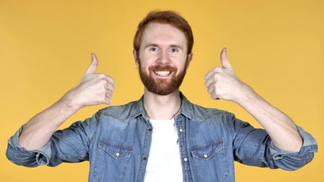kızıl saçlı adam üzerinde izole sarı arka plana yaşasın el hareketi - thumbs up stok videoları ve detay görüntü çekimi