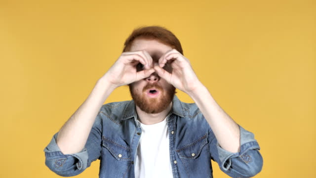 Redhead Man Searching with Handmade Binoculars Isolated on Yellow Background video