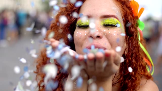 Redhead woman blowing confetti