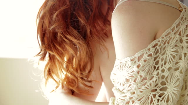 Redhead woman sitting in bed backlit by the sun  dyed red hair stock videos & royalty-free footage