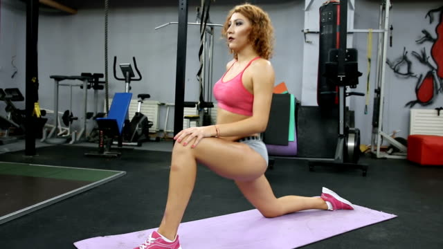 Redhead woman stretching leg on mat in gym fitness, sport, training and lifestyle concept - Redhead woman stretching leg on mat in gym. doing the splits stock videos & royalty-free footage