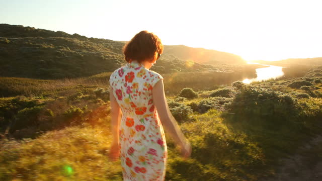 Redhead woman walking on pathway in nature