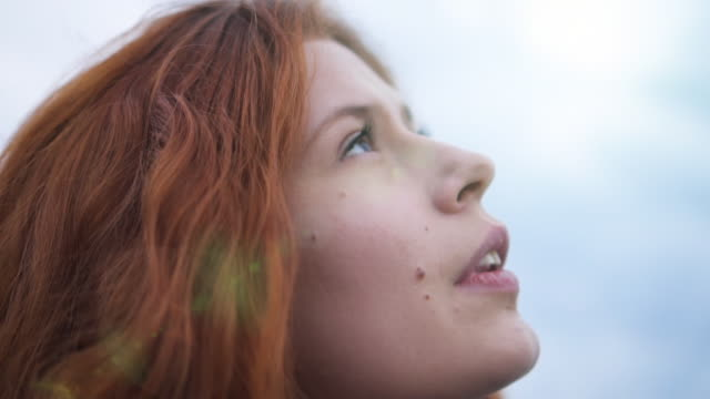 redhead young woman looking up to sunset sky with hope pray prayer sun flare - looking up stock videos & royalty-free footage