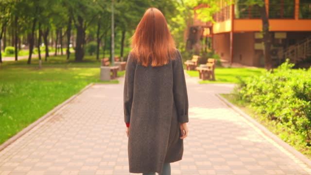 donna d'affari dai capelli rossi che cammina lungo il vicolo al rallentatore - capelli rossi video stock e b–roll