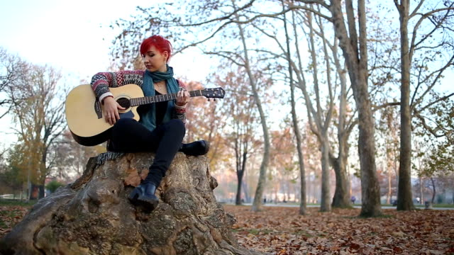 Redheaded Woman Playing Acoustic Guitar Sitting On a Tree Stump video
