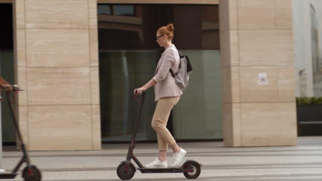 red-headed woman using eco friendly vehicle - monopattino elettrico video stock e b–roll