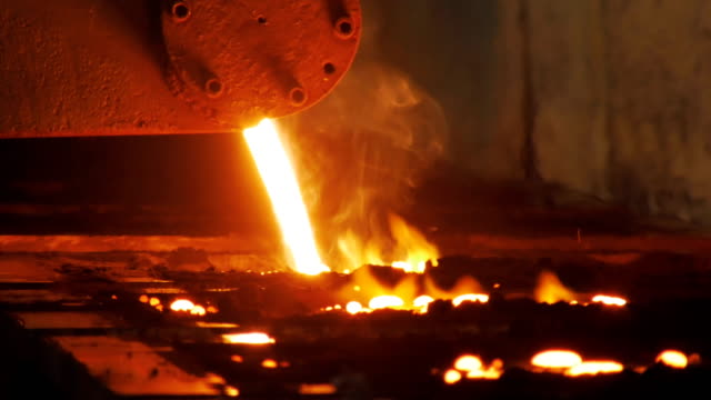 red-hot aluminium is pouring in black trolleys, smelting shop in metallurgical factory, close-up - acciaio video stock e b–roll