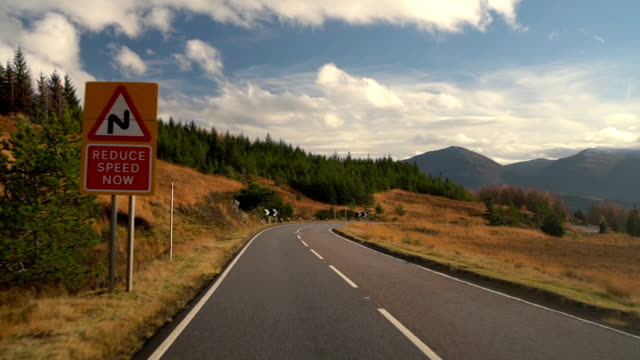 reduce speed sign in the beautiful autumn road trip in scotland - highlands scozzesi video stock e b–roll