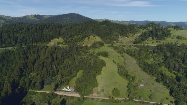 redwoods auf hügeln und eine kleine farm am redwood highway 101 in der nähe von garbeville, kalifornien, usa am sonnigen frühlingstag. beschleunigtes drohnenvideo mit der vorwärts-kamerabewegung. - staatspark stock-videos und b-roll-filmmaterial