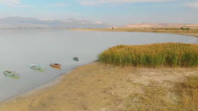 schilf, wiese und boote in karatas lake - schilf stock-videos und b-roll-filmmaterial