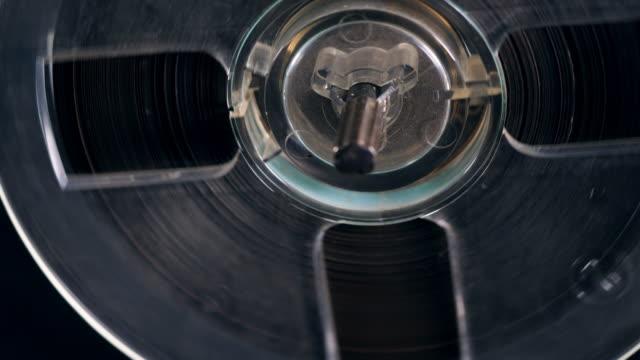 reel recorder spins a bobbin with tape. - bobina apparecchiatura di registrazione del suono video stock e b–roll