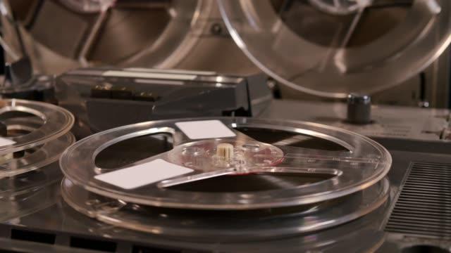 reel to reel taperecorder playing music - bobina apparecchiatura di registrazione del suono video stock e b–roll