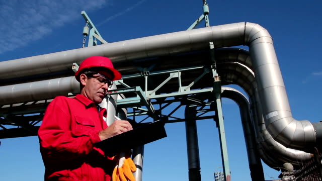 Refinery Worker and Pipelines Worker wearing red overalls and hardhat , writing on clipboard next to pipelines. HD1080p.  gas pipe stock videos & royalty-free footage