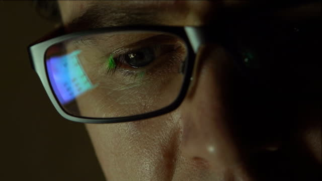 Reflection at the glasses of young man: looking a site video