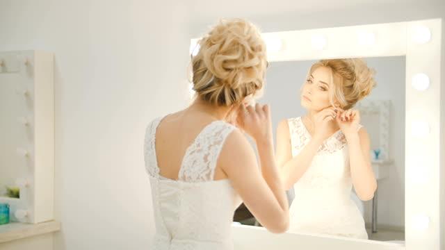reflexion in einem spiegel von einem schönen mädchen ohrringe nahaufnahme aufsetzen - ohrring stock-videos und b-roll-filmmaterial