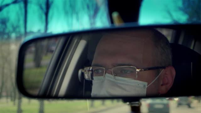 stockvideo's en b-roll-footage met bezinning in achtermeningspiegel van de mens in beschermend medisch masker dat auto door stad tijdens uitbarsting van gevaarlijke ziekte rond wereld drijft - mirror mask