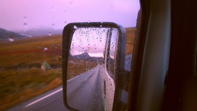 Reflection in camping van mirror on road trip