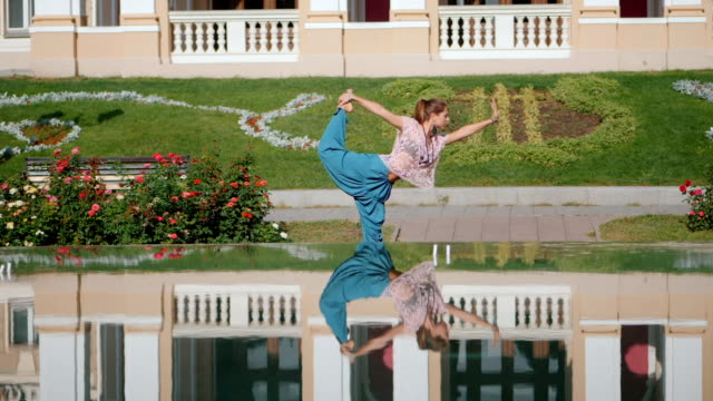 Reflection in the water of a sportive woman making stretching bent during workout in the city. Girl practicing yoga near fountain, beautiful architecture background. Slow motion video
